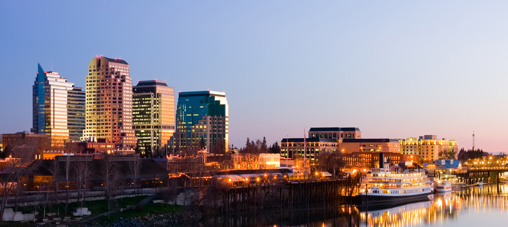 image of Sacramento city's harbor at dusk, with the city on the left and in the background. There's a dock and paddle boat on the right, in the foreground.